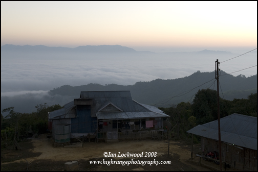 Looking east from Hmuifang at dawn, showing an idyllic home and a distant cloud bank in a valley (a phenomena known as ronei in Mizo)