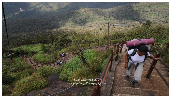 Sonalee Abeyawardene and students from OSC ascending the Hatton path steps to Sri Pada shortly after joining the concrete steps from the fishing hut trail. The Japanese Dagoba is visible on the regular Hatton pathway.