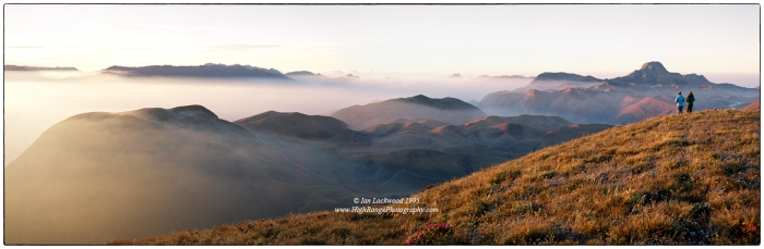"Looking south over the 2,000 meter high Eravikulam plateau from Kattu Malai. The sunrise highlights the extensive ""downs"" of the shola/grasslands complex that is uniquely preserved in this magical National Park. Anai Mudi's distinctive hat profile is on the right horizon while the edges of the Palalni Hills are on the far left. My father Merrick and cousin Anna are at the edge taking in an unforgettable Western Ghats experience."