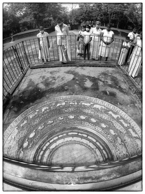 Visitors wearing personal protective gear appreciate the moonstone at Mahasena's palace in Abhayagiri, Anuradhapura. This is the most well-known moonstone in Sri Lanka and is appreciated for its fine craftsmanship and stunning detail.