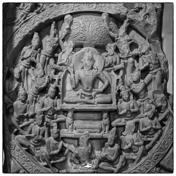 A richly carved panel from the Amarāvatī Stupa housed in the Chennai (Madras) Museum. The image depicts the Buddha giving a sermon under the bodhi tree. It appears that at some point in its life someone has made an effort to remove facial representations from this piece of limestone.